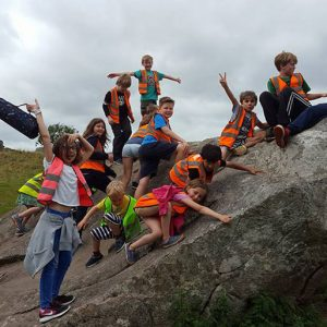 Children on Avebury stone in Savernake Avenue Holiday Club