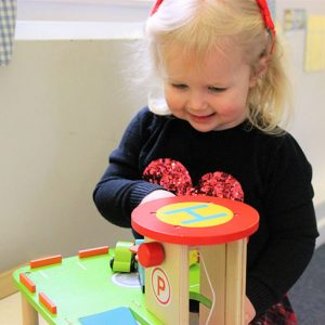 Child playing with toy garage in Bluebells room Andover
