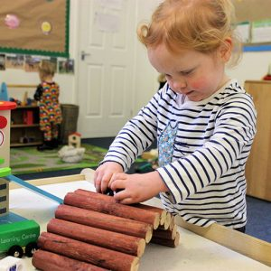 Child playing with mini logs in Bluebells room Andover