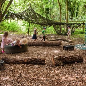 Children playing in woodland area in Andover nursery