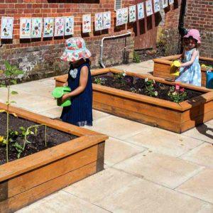 Children watering raised flower beds in Andover nursery