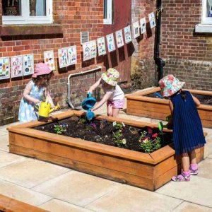 Children watering flowers in garden of Andover nursery