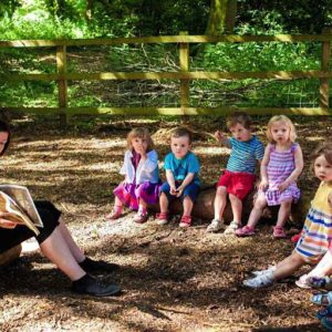 Children enjoying a story read by member of staff in woodland area in Andover nursery