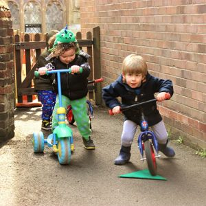 Children playing on bikes in garden in Marlborough nursery