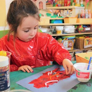 Child painting in Marlborough nursery