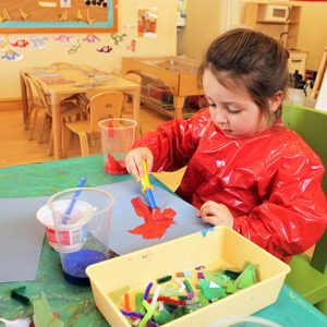 Child painting at table in Marlborough nursery