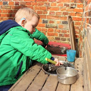 Child playing in mud kitchen in the garden of Marlborough nursery