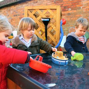 Children playing with water and boats in the garden at Savernake nursery