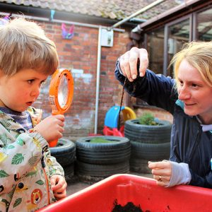 Children playing with magnifying glass in the garden at Savernake nursery
