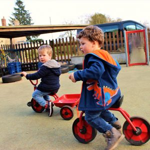 Children playing on tricycles in the garden at Savernake nursery
