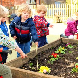 Children playing at the raised flower beds in the garden at Savernake nursery