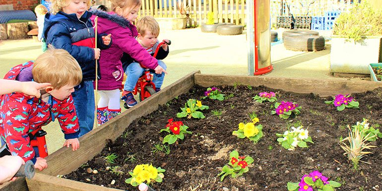 Children playing at the flower beds in the garden at Savernake nursery