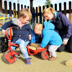 Playing with the tricycles in the garden at Savernake nursery