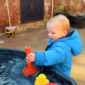 Child playing with water in the garden at Savernake nursery