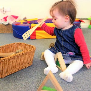 Child playing with wooden kitchen utensils in the Snowdrops room Andover